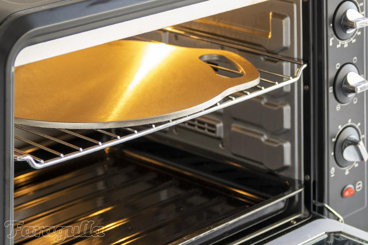 Coloca la plancha Pizza Pro de Faragulla en la rejilla más alta del horno
